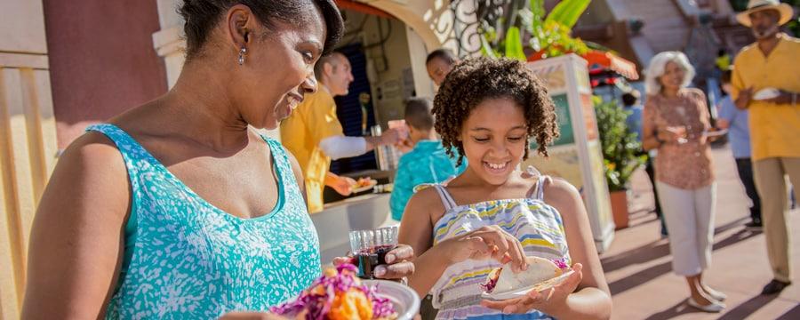 Mãe e filha sorriem antes de saborear tacos de peixe no Epcot International Food & Wine Festival