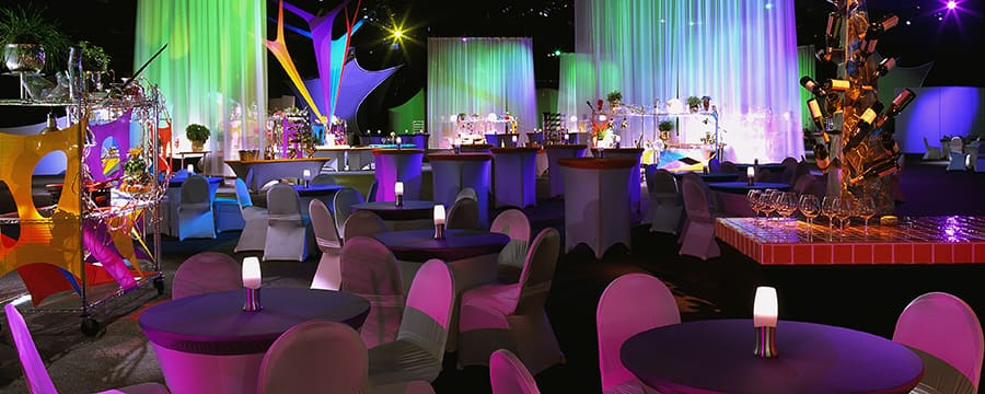 A dark indoor dining area brightened by neon lights, and decorated with wine bottles and cooking supplies