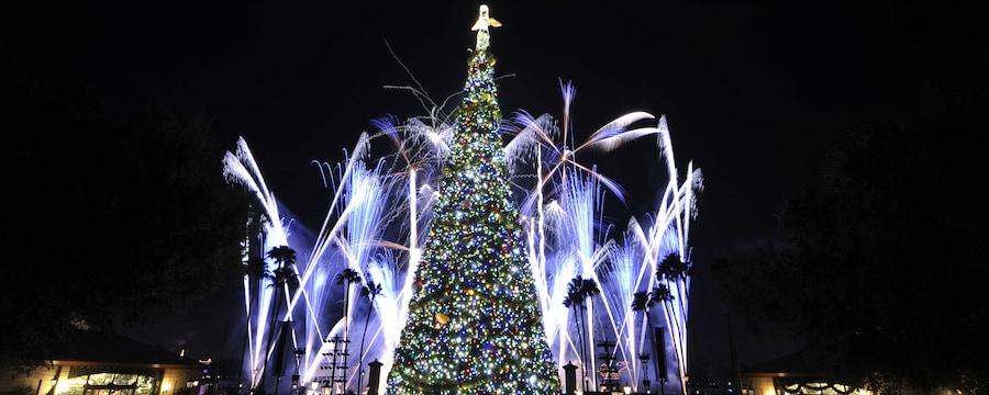 Uma árvore decorada com luzinhas natalinas e um anjo no topo perto de uma multidão de pessoas, árvores e fogos de artifício
