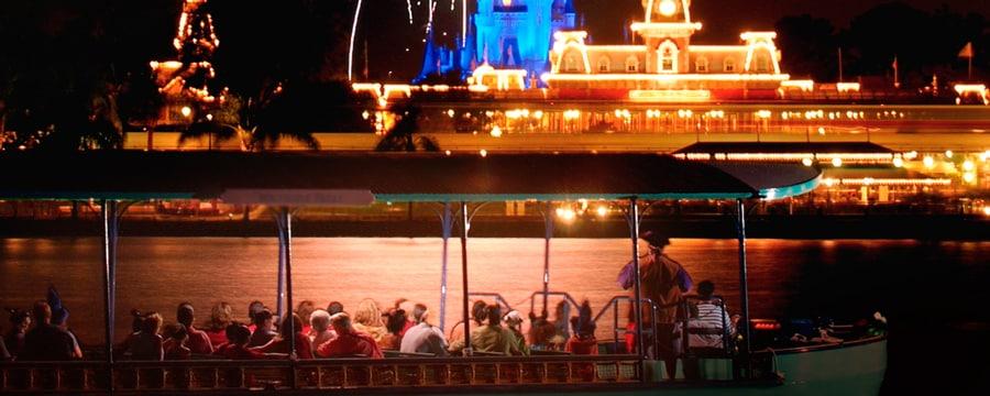 Cinderella Castle iluminado em roxo com fogos de artifício estourando no céu sob os olhares de Visitantes em um barco