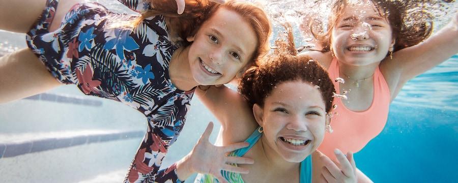 Tres niñas sonríen bajo el agua mientras nadan en una piscina en un hotel Good Neighbor de Walt Disney World