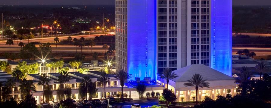 Hotel con luces encendidas de noche y palmeras