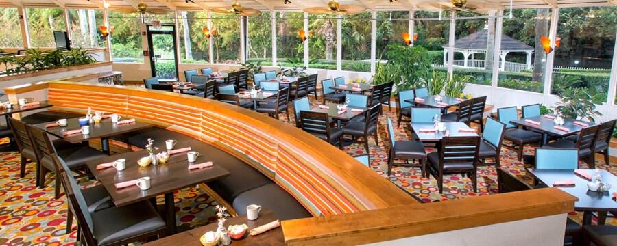 Restaurante con mesas preparadas, sillas y vista de un paisaje con palmeras y un gazebo