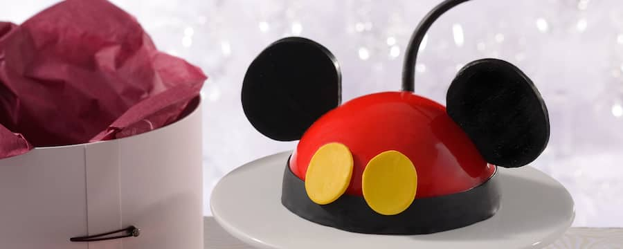 A Mickey Mouse dome cake on a pedestal next to Amorette's elegant hat box packaging