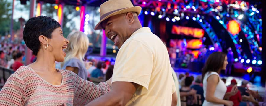 A laughing couple dances near a stage and a crowd of people