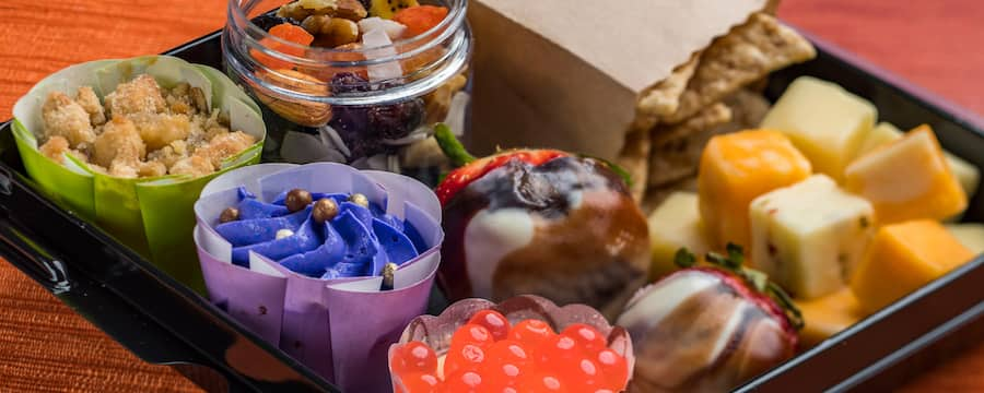 Adult snack box with chocolate dipped strawberries, cheesecake, chocolate cupcake, apple crisp, California trail mix, cheese cubes and crackers