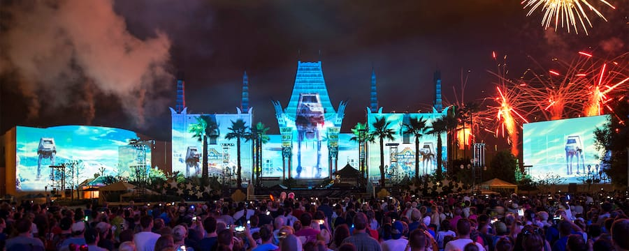 Guests watch the Star Wars Galactic Spectacular in front of an illuminated Grauman's Chinese Theatre that has state of the art effects of AT AT Walkers projected on its exterior