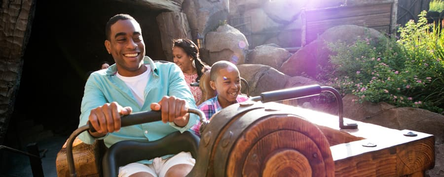 A family of 4 holds smiles as they ride aboard Seven Dwarfs Mine Train