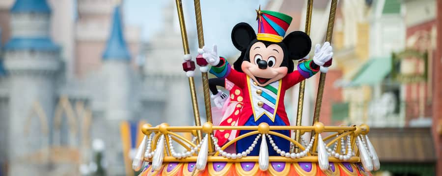 Mickey Mouse dressed in a festive costume waves excitedly during the Disney Festival of Fantasy Parade