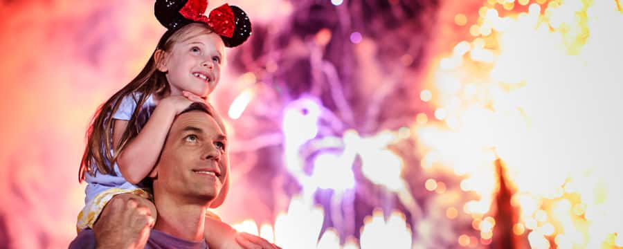 A daughter in a Minnie Mouse Ear Hat rides on her dad's shoulders as fireworks explode above them