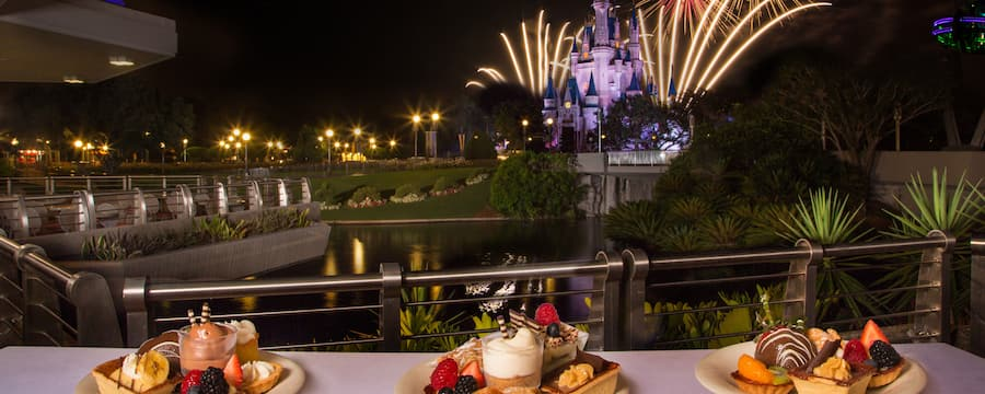Desserts on display at Tomorrowland Terrace Restaurant as fireworks explode above Cinderella Castle