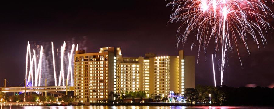 El área de la piscina en Disney's Contemporary Resort iluminada a la noche con una vista de los fuegos artificiales