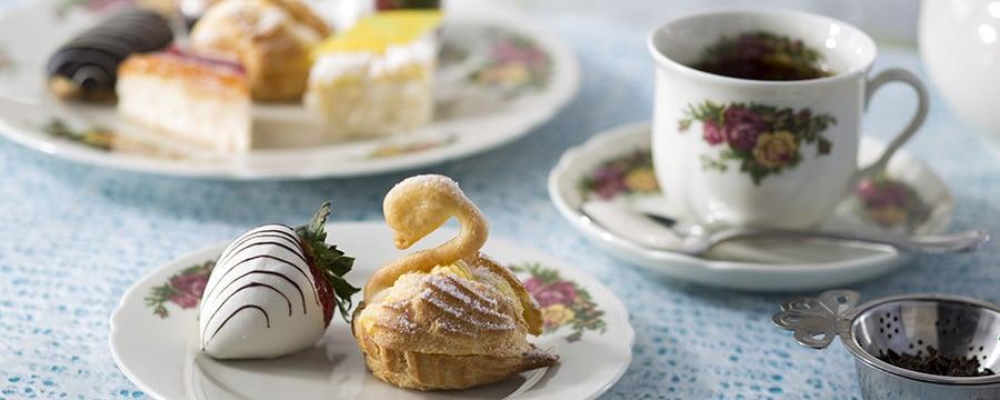 Fresa bañada en chocolate blanco, panecillos en forma de cisnes y té negro servido en un florido juego de té de porcelana inglesa