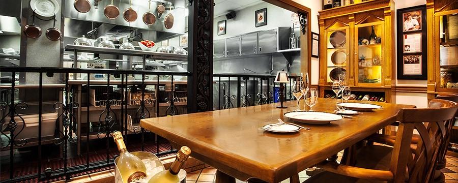 Conjunto de mesas em madeira para 2, em frente à cozinha da mesa do chef no Victoria and Albert's