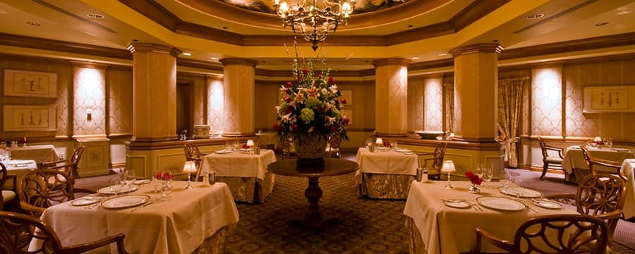 A luscious bouquet basking beneath the glow of a chandelier in the middle of an elegant dining room