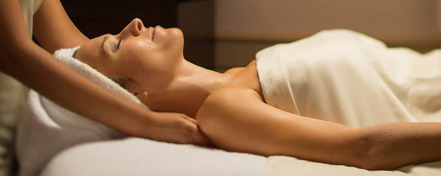 A masseuse at Senses – A Disney Spa massages the shoulders of a woman lying on her back