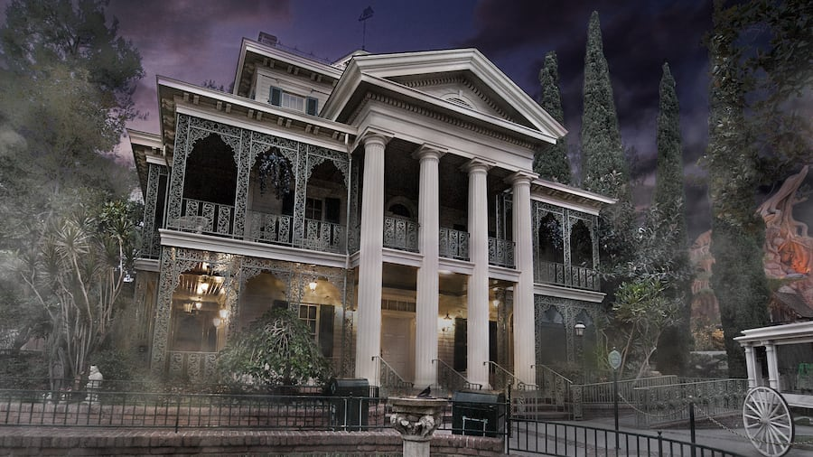 A gloomy night engulfs the Haunted Mansion, a 3 story building with pillars and a grid iron fence