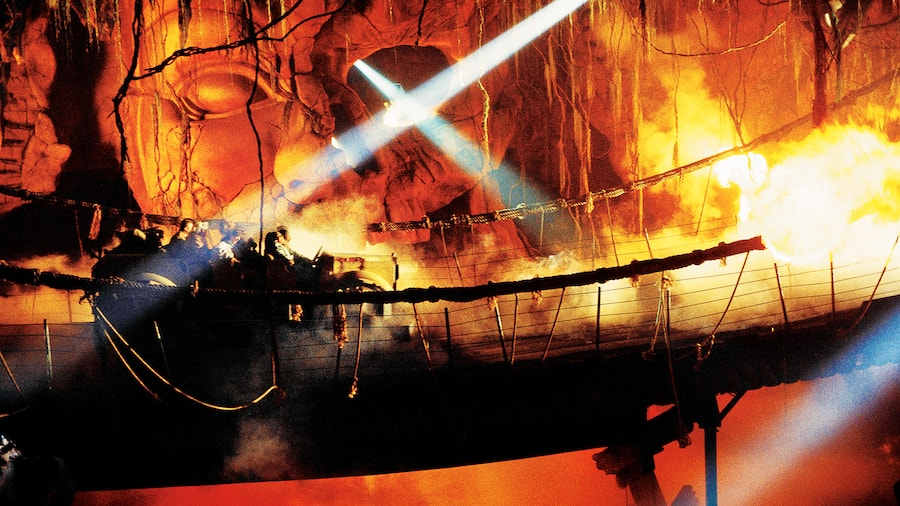 Passengers ride in a pirate ship across a fiery sea in the Indiana Jones Adventure attraction