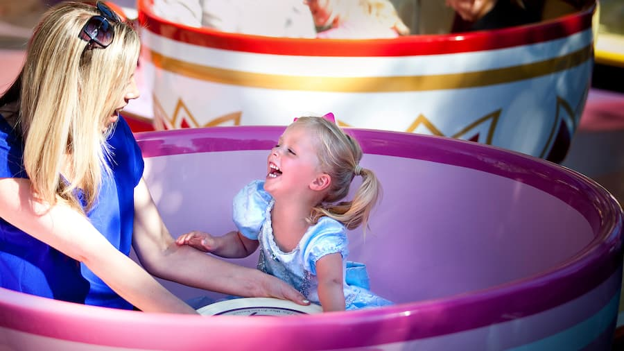 A laughing mother and toddler daughter sit in a spinning oversized teacup