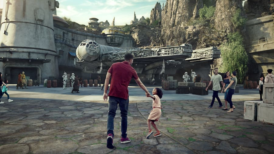A parent and child excitedly approach a star ship at Star Wars Galaxy's Edge