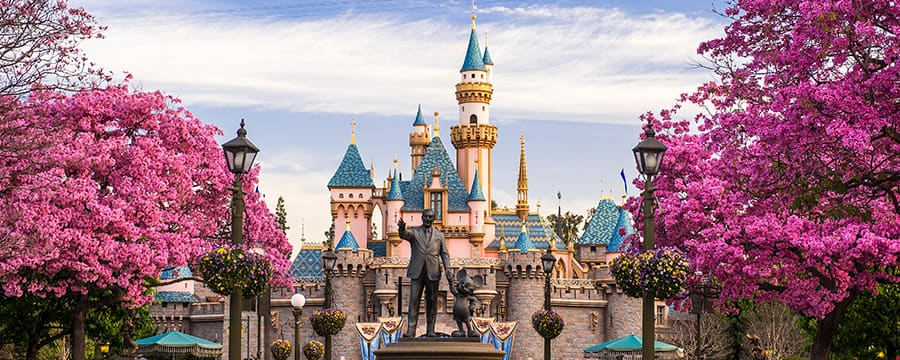 A statue of Walt Disney and Mickey Mouse in front of Sleeping Beauty Castle