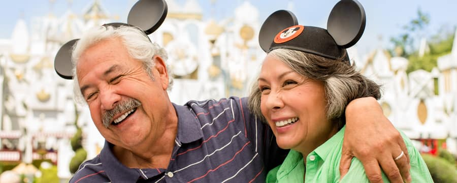 A couple smiles while wearing Mickey ears