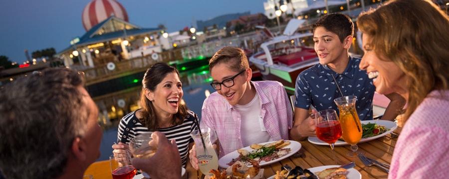 船のドックにあるピクニックテーブルで夕食を食べる家族