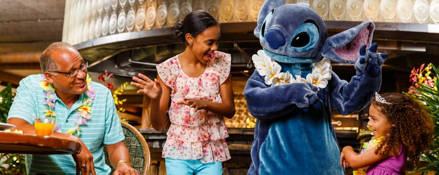 A mother and daughter dance with Stitch, while a man looks on
