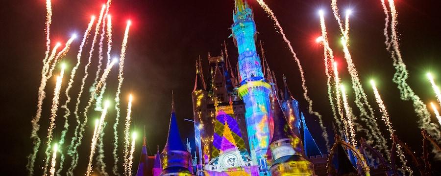 Los fuegos artificiales estallan sobre Magic Kingdom Park al mismo tiempo que vibrantes efectos de luz iluminan Cinderella Castle