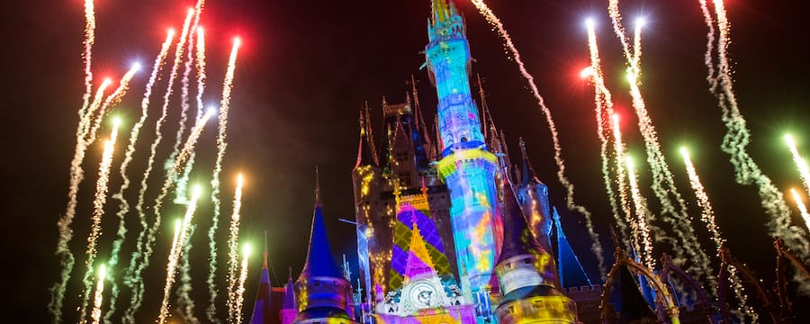 Fireworks blast off above Magic Kingdom park as vibrant lighting effects illuminate Cinderella Castle
