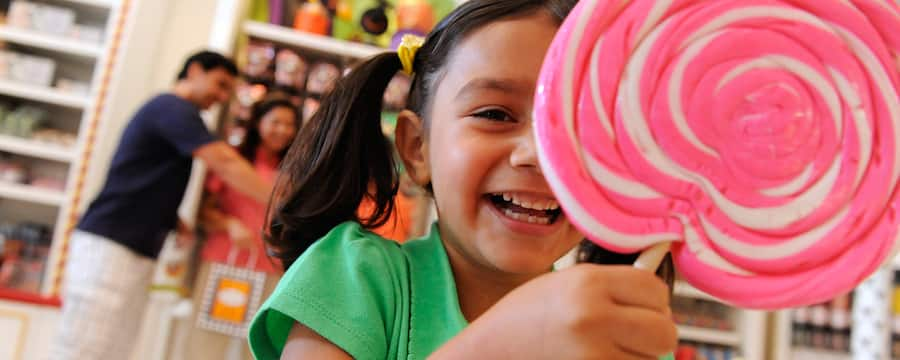 A young girl in a candy shop smiles as she holds her giant pink and white swirled lollipop and her parents shop in the background