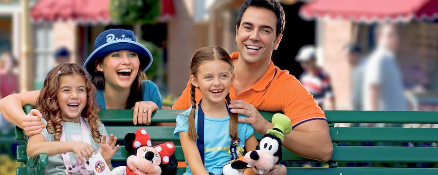A family enjoys a magical moment of laughter as they sit on a bench at a Disney Theme Park