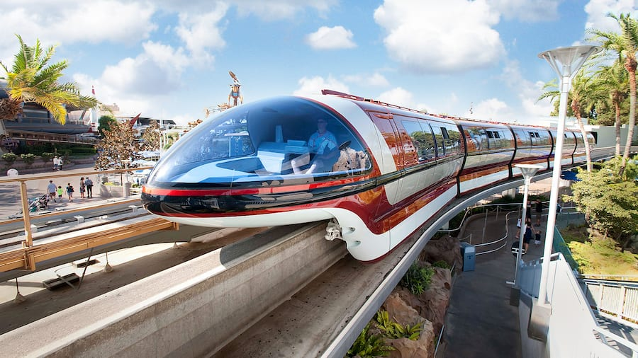 The Disneyland Monorail near walkways and trees