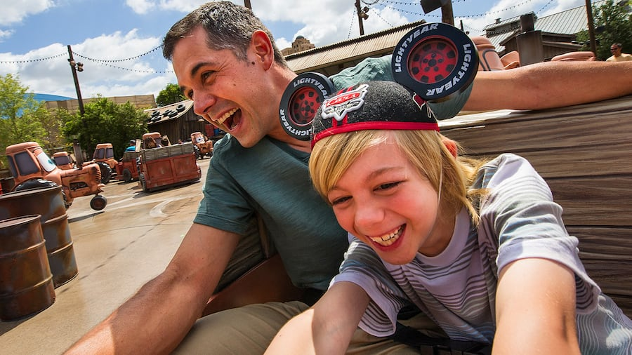 A man and a smiling boy wearing Mickey ears