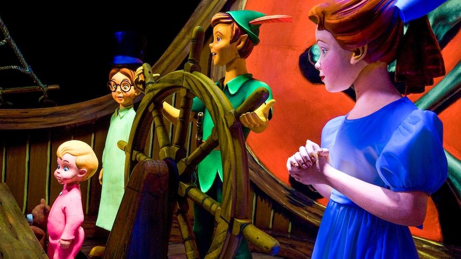 海賊船の舵輪を取るピーター・パンと、その両脇に立つウェンディ、マイケル、そしてジョン。