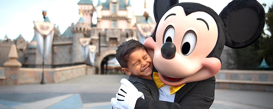 眠れる森の美女の城を背に小さな男の子とハグするミッキーマウス