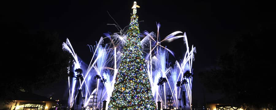 A Christmas tree with fireworks bursting behind it