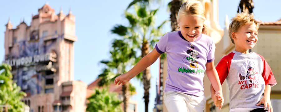A boy and girl running near palm trees