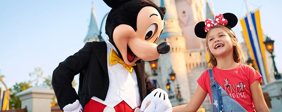 シンデレラ城の前でミニーマウスのイヤーハットをかぶり、ミッキーマウスと手をつなぐ女の子