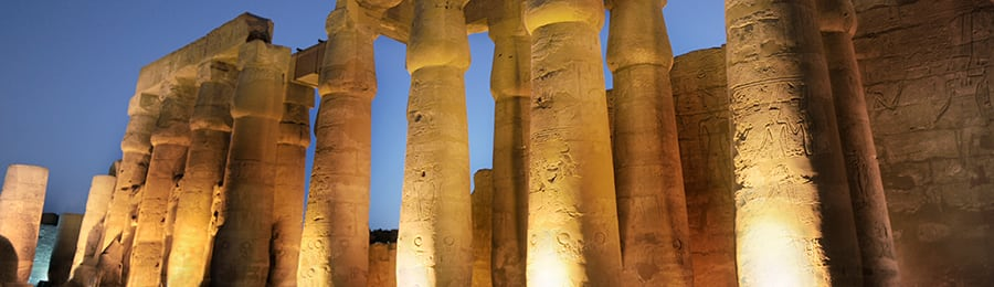 Towering, ancient Egyptian carved columns are illuminated at night