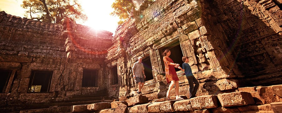 A family walks along a stone walkway at Angkor Archaeological Park