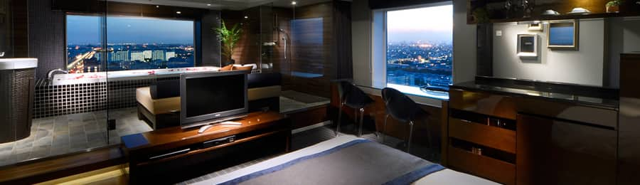 A guest room with large windows offering city views at Brighton Tokyo Bay hotel