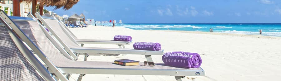 A row of 4 lounge chairs topped with beach towels, located on a sandy beach facing the sea