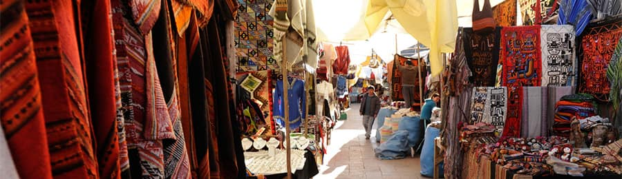 A local market with shops displaying patterned cloths and garments