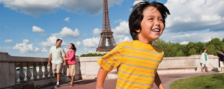 A young boy running near the Eiffel Tower