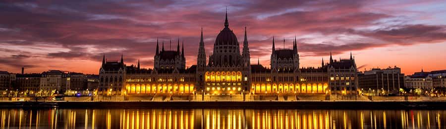 Lights reflect on the water from the Hungarian Parliament Building in Budapest, Hungary