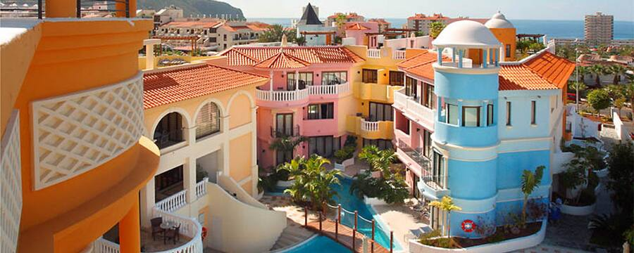 Brightly colored resort buildings and an outdoor pool at Silverpoint Paramount in Tenerife