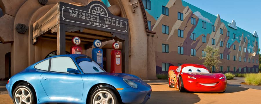 Lightning McQueen and Sally Carrera parked in front of a hotel building