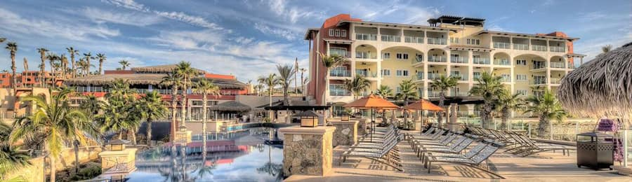 The exterior of Sirena de Mar by Welk Resorts during the day with chaise lounge chairs facing a plunge pool