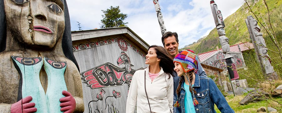 A family standing by traditional Native American totem poles and buildings